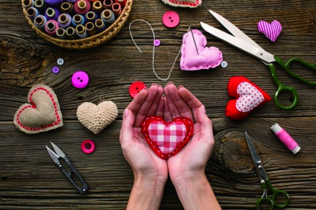 hands-holding-red-heart-shape-wooden-background